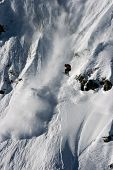 Rider jump from big rock in avalanche pic.