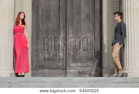 Elegant Young Couple Separated By Big Wooden Door