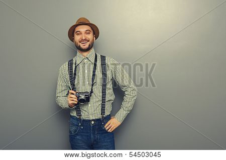 laughing hipster man holding retro camera over grey background