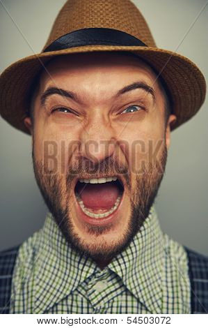 aggressive man in straw hat over grey background