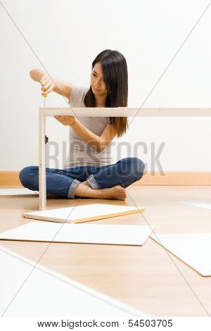Asian woman using strew drive for assembling closet