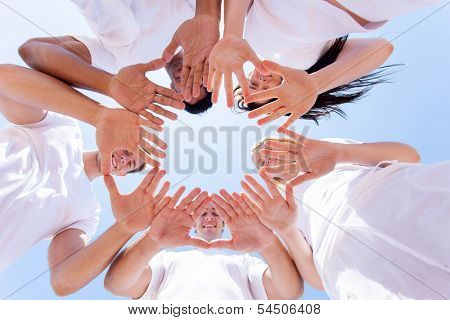 underneath view of happy people hands together outdoors