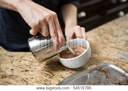 Midsection of barista making cappuccino at counter in coffeeshop