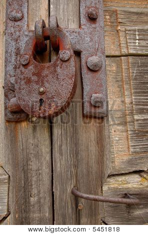 Padlock And Handle On Wooden Gate