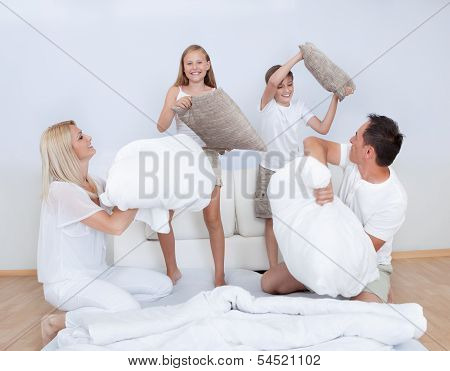 Family Having A Pillow Fight Together On Bed