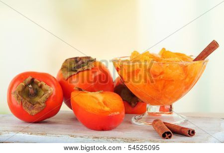 Ripe persimmons with jam in glass saucer and cinnamon on table on bright background