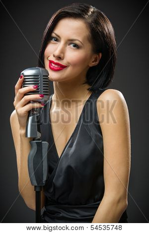 Half-length portrait of female musician wearing black evening dress and handing microphone on grey background. Concept of music and retro fashion