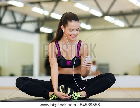 fitness, sport, training, gym, technology and lifestyle concept - smiling woman with smartphone
