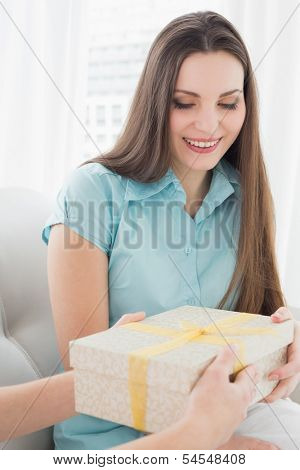 Beautiful young brunette receiving a gift box on sofa at home