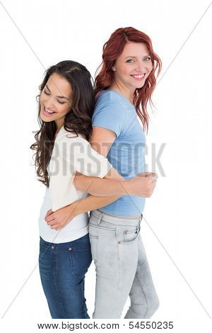 Side view of two young women standing back to back with interlocked hands over white background