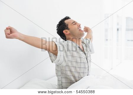 Side view of a happy young man waking up in bed and stretching his arms