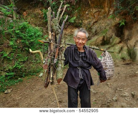 Old Man Asian, With Bunch Fagots, Goes On Mountain Trail.