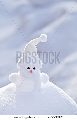 Little white snowman on the snowbank.