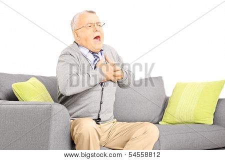 Senior man seated on a sofa having a heart attack, isolated on white background