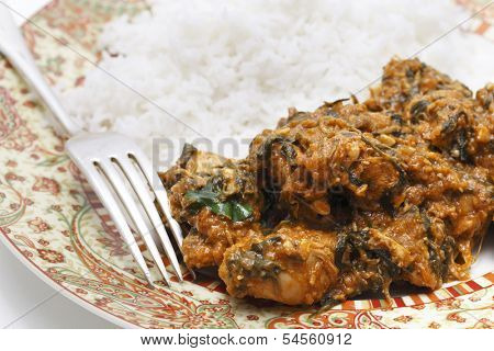 Methi murgh - chicken cooked with fresh fenugreek leaves on a plate with basmati rice and a fork