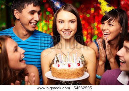 Portrait of joyful girl with birthday cake surrounded by friends at party