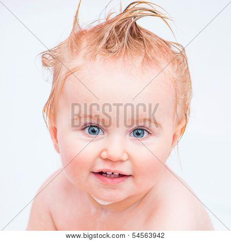 cute 1 year-old girl bathes in a bath with foam closeup