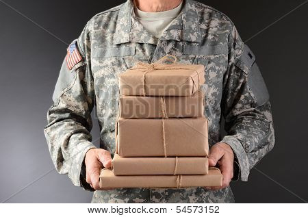 Closeup of a soldier wearing camouflage fatigues holding a stack of packages for mail call. Horizontal format, man is unrecognizable.