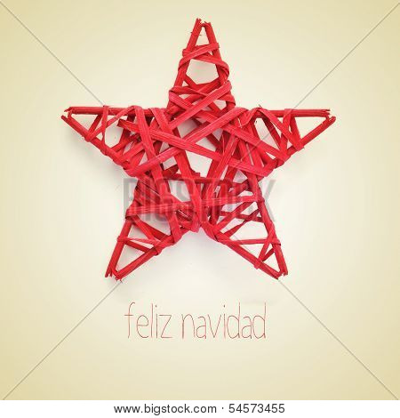 a red christmas star and the sentence feliz navidad, merry christmas written in spanish, on a beige background, with a retro effect