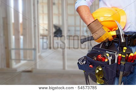 Worker with a diy tool belt over construction background