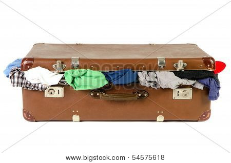 Old Suitcase Full With Clothes Before White Background