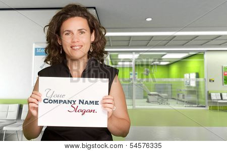 Woman holding a blank board in a hospital interior
