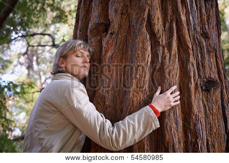 Young woman hugging a tree with closed eyes