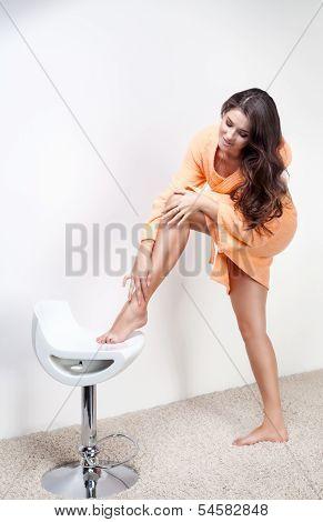 Beautiful woman shaving legs or doing skincare