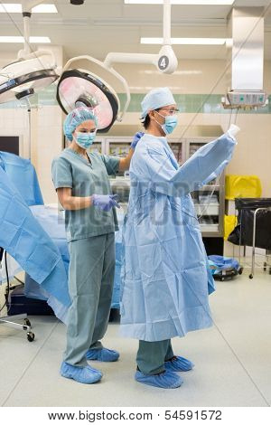 Full length of young nurse assisting doctor in wearing operation gown in hospital