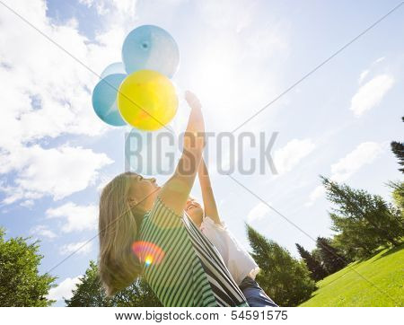 Mother and daughter playing with helium balloons in summer park