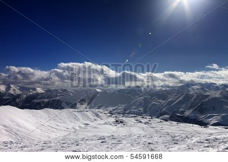 Ski Slope And Blue Sky With Sun Rays