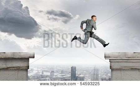 Young businessman jumping over bridge gap. Risking in business