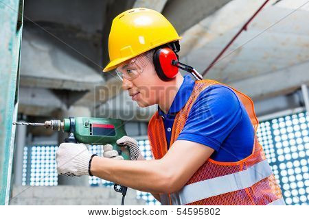 Asian Indonesian builder or worker drilling with a machine or drill, ear protection and hardhat or helmet  in a wall of a tower building or construction site