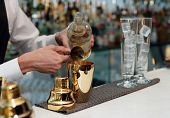 Bartender is pouring liquor in golden shaker