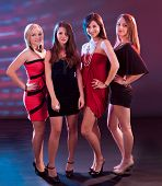 image of jive  - Group of glamorous young women in evening attire dancing together at a nightclub or disco - JPG