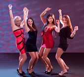 stock photo of jive  - Group of glamorous young women in evening attire dancing together at a nightclub or disco - JPG