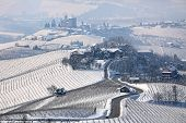 Narrow road through hills and vineyards covered with snow towards small village in Piedmont, Norther
