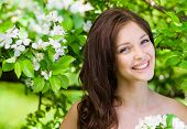 image of nearly nude  - Portrait of young woman near the flowered tree in the park - JPG