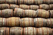 image of malt  - Stacked pile of old whisky and wine wooden barrels and casks