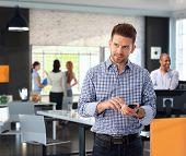 stock photo of coworkers  - Casual businessman using mobile phone at modern stylish office - JPG