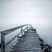 stock photo of pier a lake  - Old ruined wooden pier perspective on the lake in foggy morning - JPG