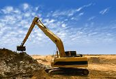 picture of oversize load  - Orange excavator at Construction irrigation canal in Desert - JPG