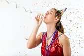 Woman celebrating birthday or new years eve and hooting with horn at a shower of confetti