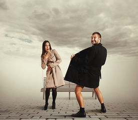 foto of exhibitionist  - startled young woman looking at crazy man in coat on the street - JPG
