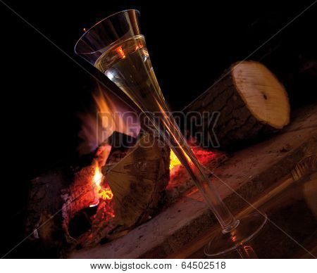 A cup of champagne near fireplace, at home in winter. Warm and romantic atmosphere