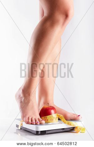 A Pair Of Female Feet Standing On A Bathroom Scale With Red Apple