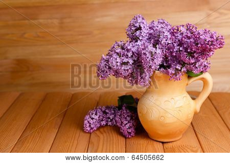 Beautiful lilac flowers in pitcher on table on wooden background