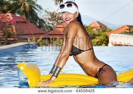 Woman With Perfect Tanned Body On Yellow Air Mattress