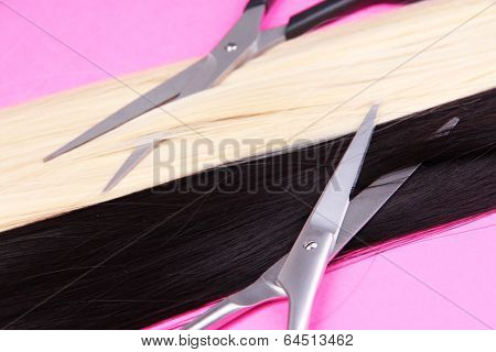 Long black and blond hair with scissors on pink background