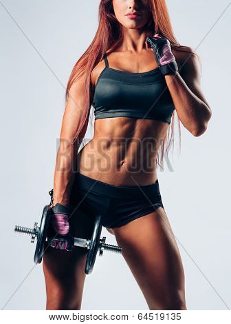 beautiful fitness female posing on studio background